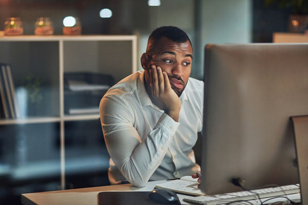 A man sitting at a computer looking bored