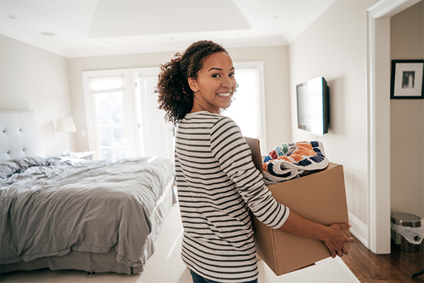 Woman carrying box of stuff in home