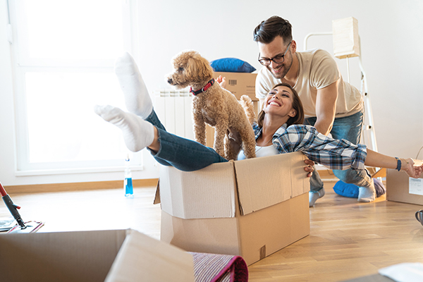 Couple unpacking their boxes with their dog