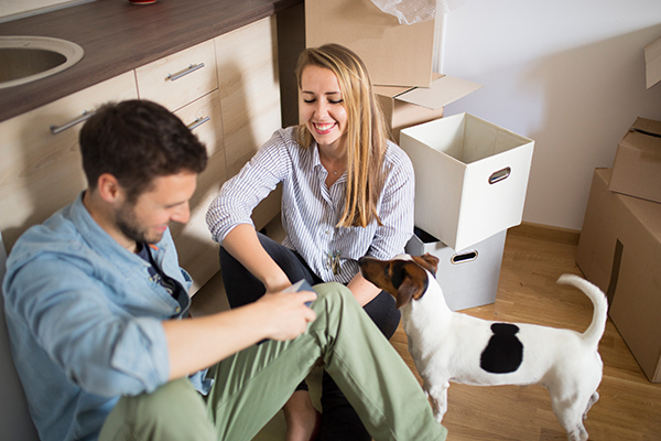 Young couple and dog unpacking boxes
