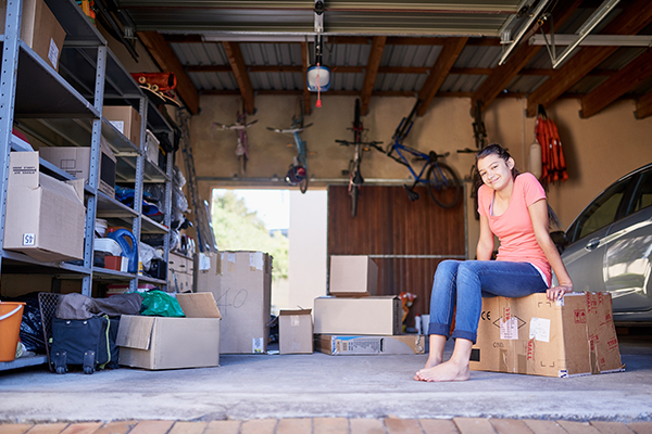 Woman sits on a box in her garage