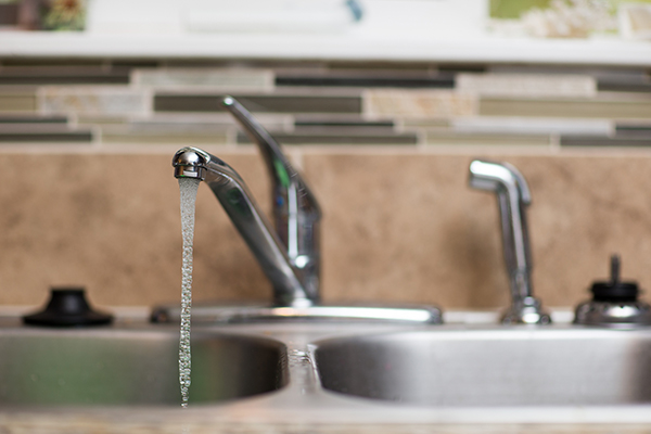 Kitchen faucet running in a home