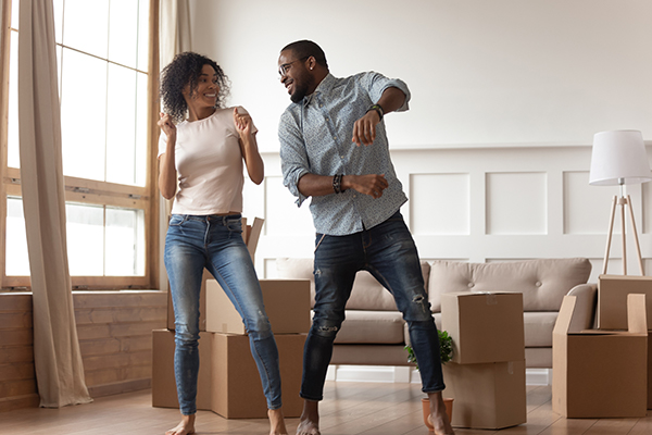 A happy couple dances in their home