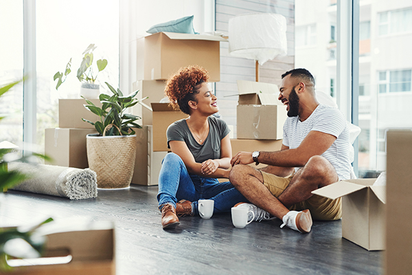 A couple sits next to the moving boxes in their new home