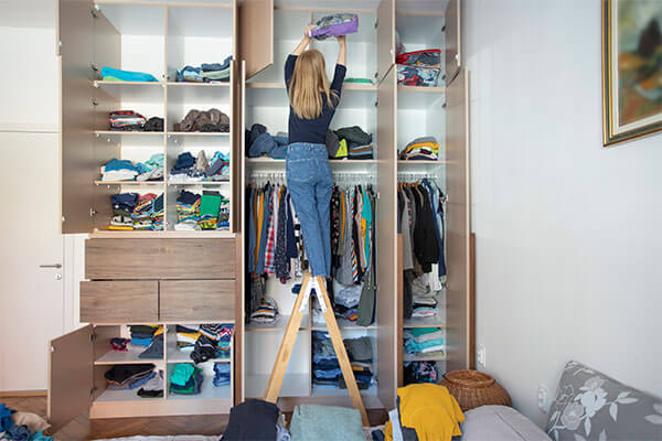 A woman is organizing her home closet