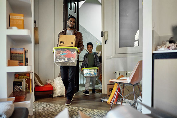A man and his son carry boxes into a room