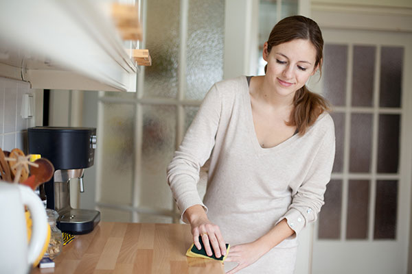 A woman cleans her kitchen countertops.