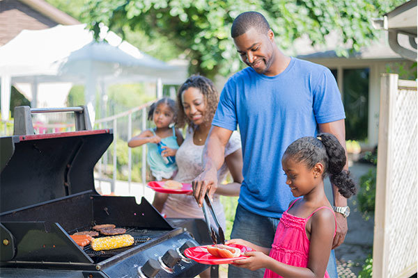 A family stands around a grill ready to eat