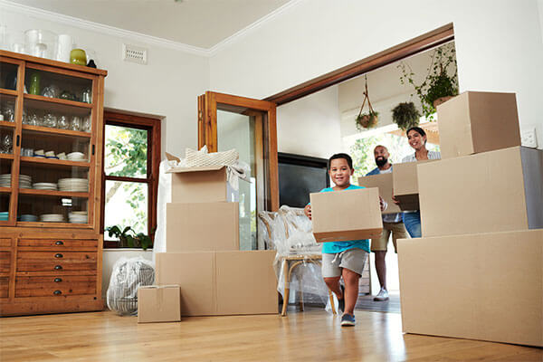 A family brings boxes into a home.