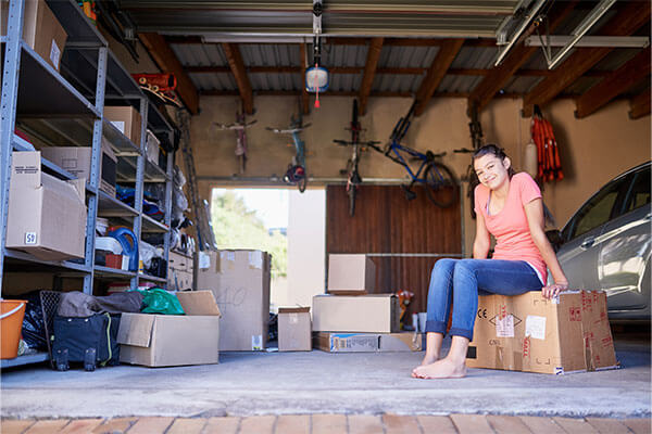 A woman sits on a box in a garage